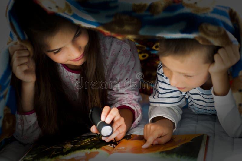 Crianças que lêem na noite foto de stock