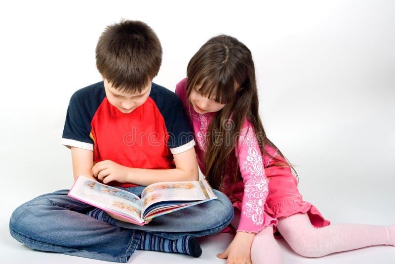 Crianças que lêem um livro fotografia de stock royalty free
