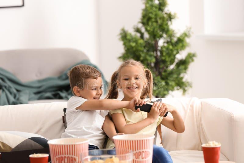 Crianças que lutam pelo controlo a distância ao olhar a tevê em casa fotos de stock royalty free