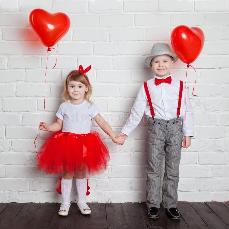 Crianças que mantêm e que escolhem balões do coração O dia de Valentim e o conceito do amor, no fundo branco imagens de stock