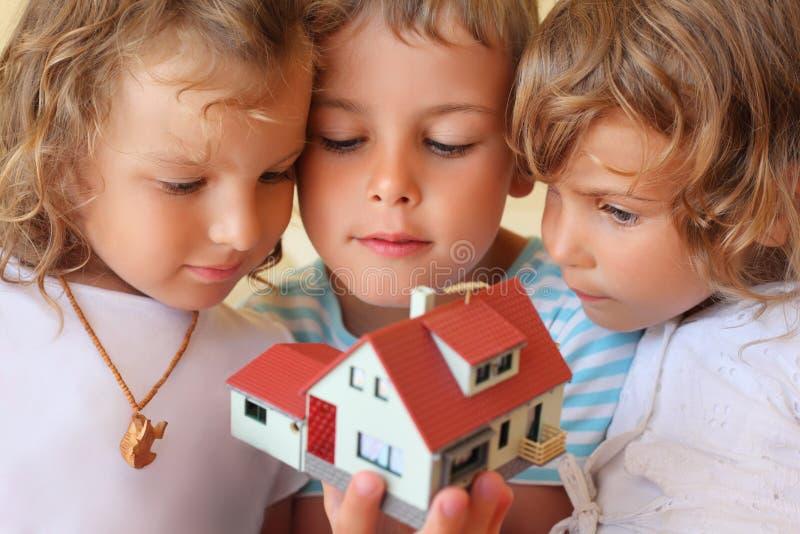 Crianças que mantêm-se junto no modelo das mãos da casa fotografia de stock