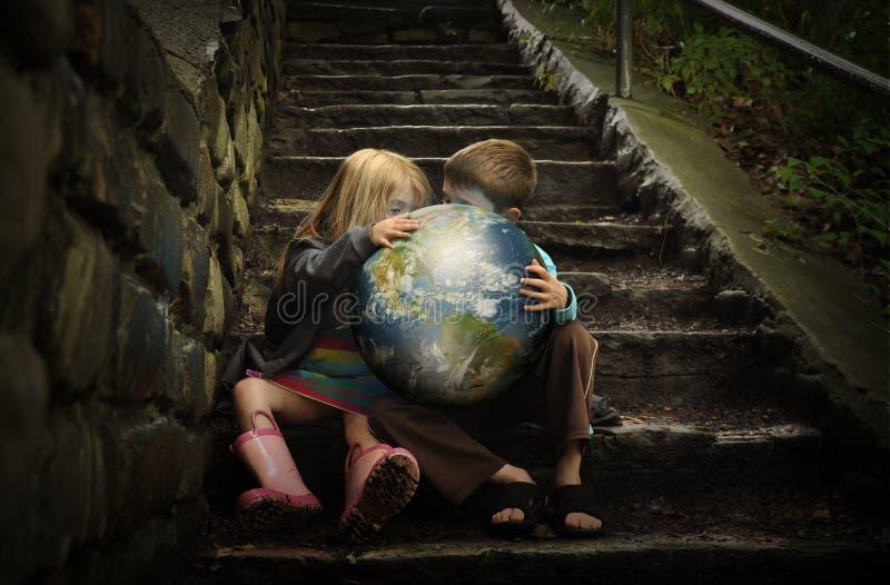 Crianças que mantêm a terra Planetin secreta fotografia de stock