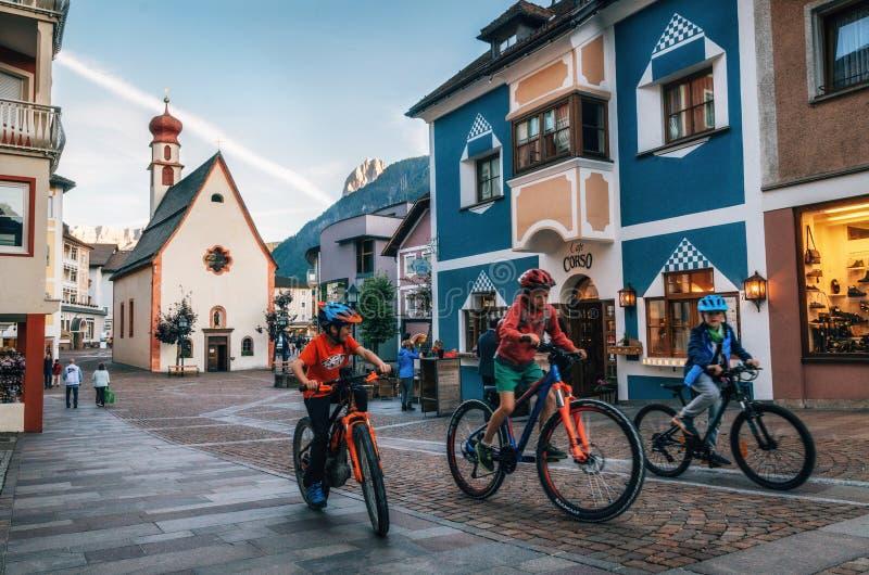 Crianças que montam bicicletas em Ortisei, Itália fotografia de stock