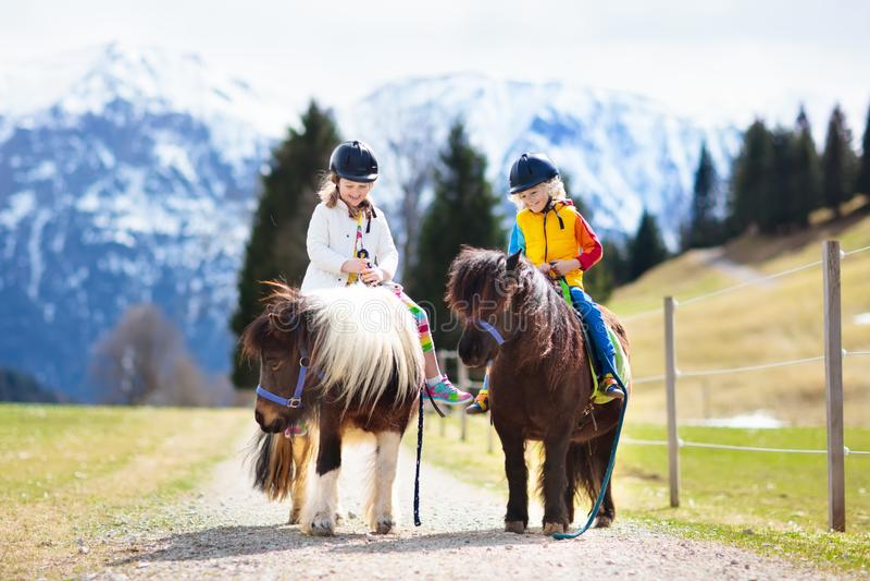 Crianças que montam o pônei Criança no cavalo em montanhas dos cumes imagens de stock
