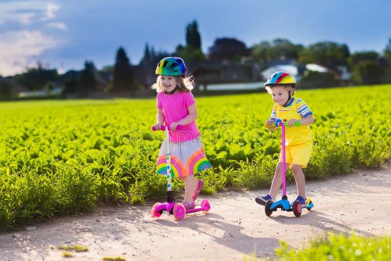 Crianças que montam o 'trotinette' no dia de verão ensolarado imagem de stock royalty free