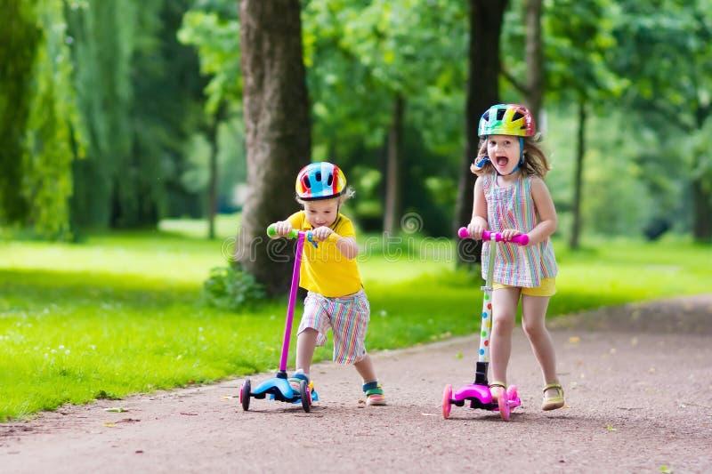 Crianças que montam 'trotinette's coloridos imagens de stock royalty free