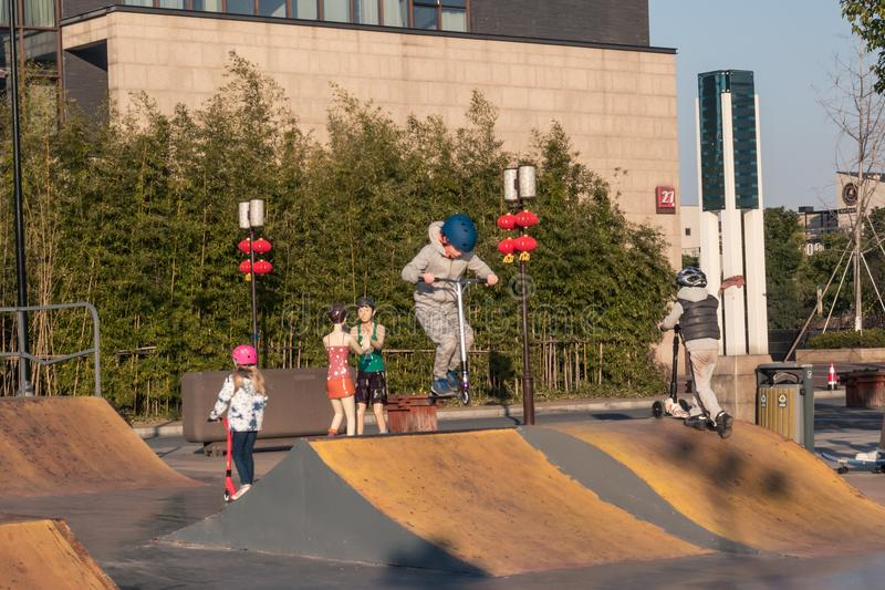 Crianças que montam 'trotinette's do pontapé no parque extremo no dia ensolarado fotografia de stock royalty free