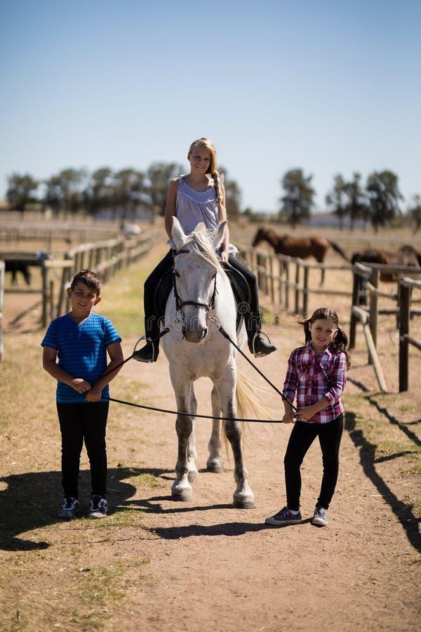 Crianças que montam um cavalo no rancho foto de stock royalty free