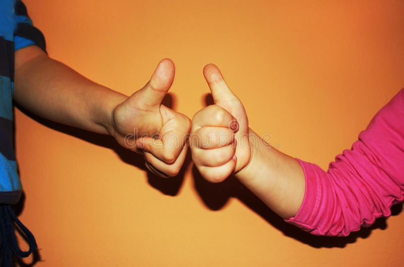 Crianças que mostram dois polegares acima no fundo alaranjado foto de stock