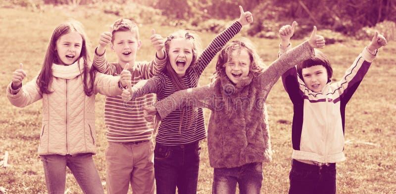 Crianças que mostram os polegares acima fora fotos de stock royalty free