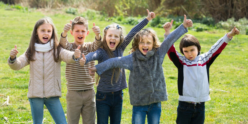 Crianças que mostram os polegares acima fora foto de stock