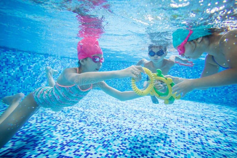 Crianças que nadam debaixo d'água e que jogam com brinquedos imagem de stock