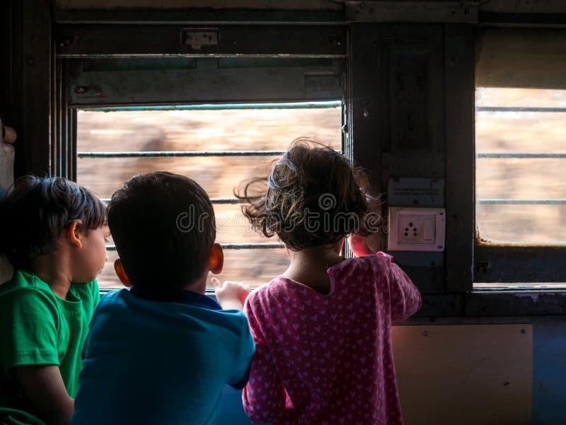 Crianças que olham a janela exterior do trem foto de stock