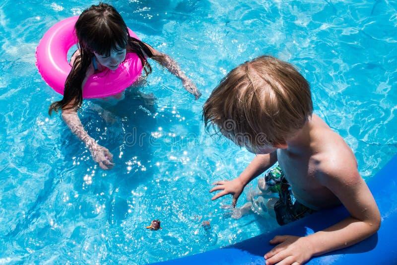 Crianças que olham o brinquedo do mergulho na piscina fotografia de stock royalty free