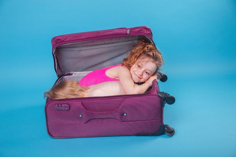 Crianças que olham para fora a mala de viagem violeta no fundo azul Apronte para o curso imagem de stock