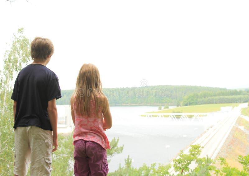 Crianças que olham uma represa fotos de stock