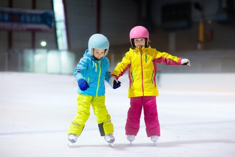 Crianças que patinam na pista de gelo interna Crianças e esporte de inverno saudável da família Menino e menina com patins de gel imagens de stock royalty free