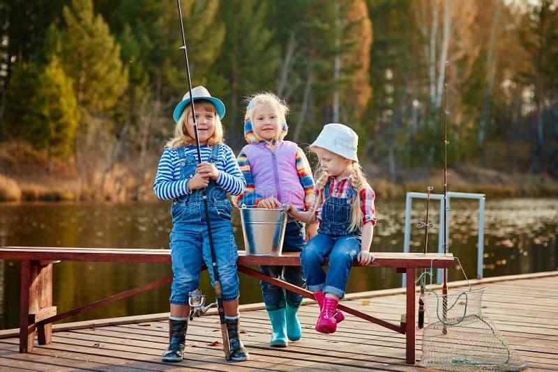 Crianças que pescam com varas de pesca Dia morno do outono Pesca em um pontão de madeira fotos de stock royalty free