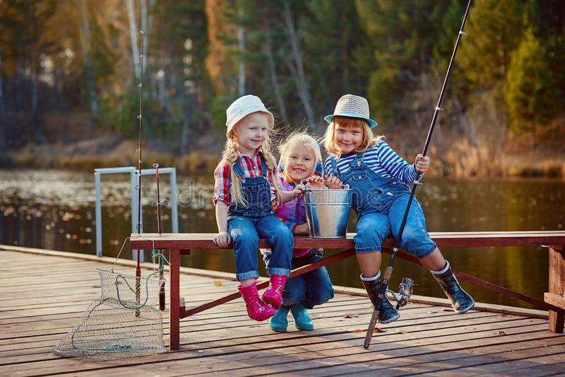 Crianças que pescam com varas de pesca Dia morno do outono Pesca em um pontão de madeira foto de stock