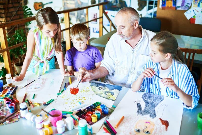 Crianças que pintam com o professor na classe de arte imagens de stock royalty free