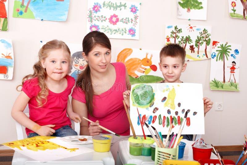Crianças que pintam com o professor na classe de arte. foto de stock royalty free