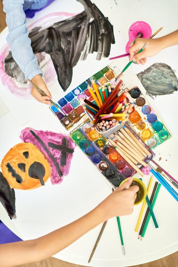Crianças que pintam imagens de Dia das Bruxas em Art Studio fotos de stock