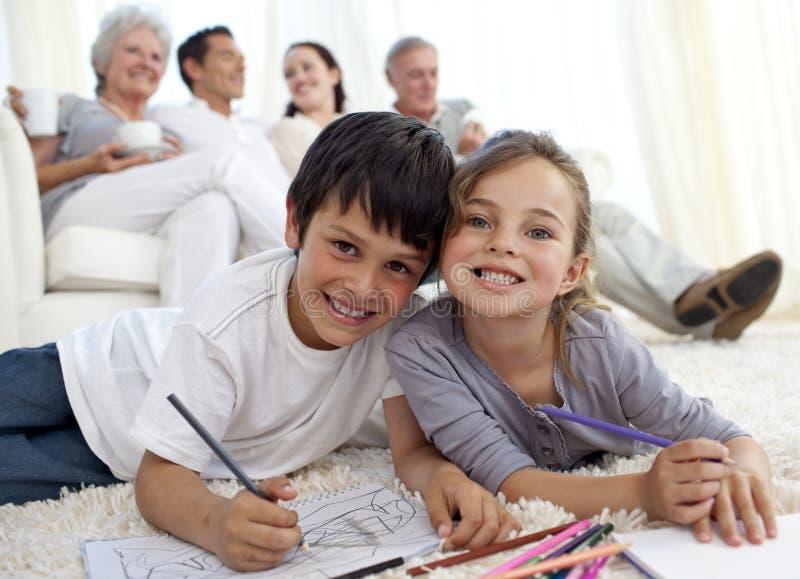 Crianças que pintam no assoalho com a família no sofá foto de stock