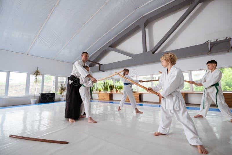 Crianças que praticam o aikido usando a posição do jo perto de seu instrutor imagens de stock royalty free