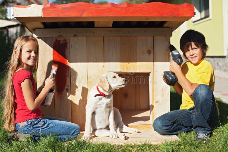 Crianças que preparam um abrigo para seu cão de cachorrinho novo imagem de stock