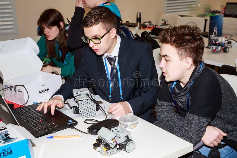 Crianças que programam o robô em competições da robótica imagens de stock