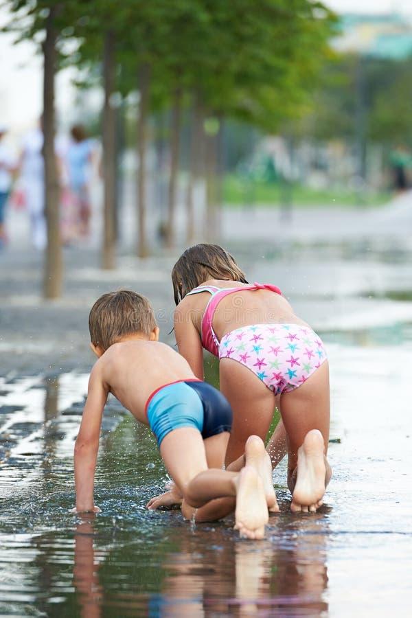 Crianças que rastejam na poça no parque fotografia de stock