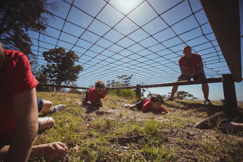 Crianças que rastejam sob a rede durante o treinamento do curso de obstáculo imagem de stock