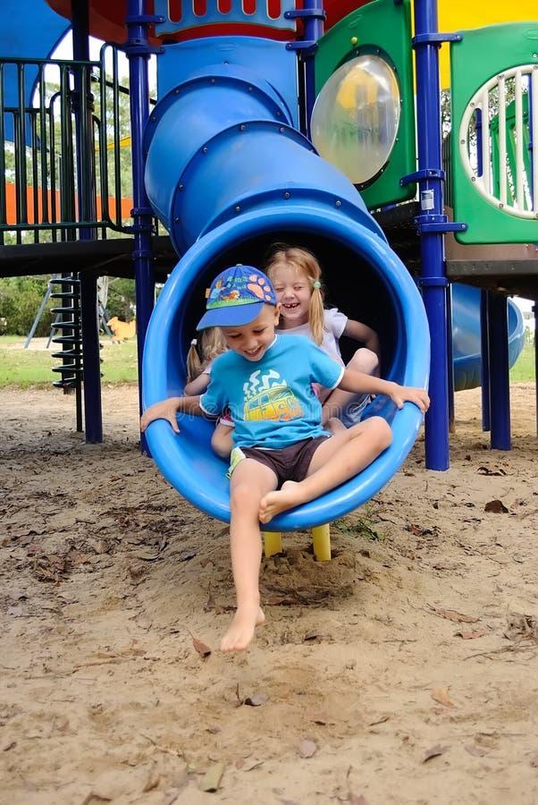 Crianças que retiram uma corrediça da câmara de ar fotos de stock royalty free