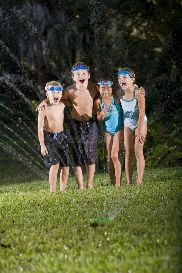 Crianças Que Riem E Que Shouting Pelo Sistema De Extinção De Incêndios Do Gramado Imagens de Stock Royalty Free