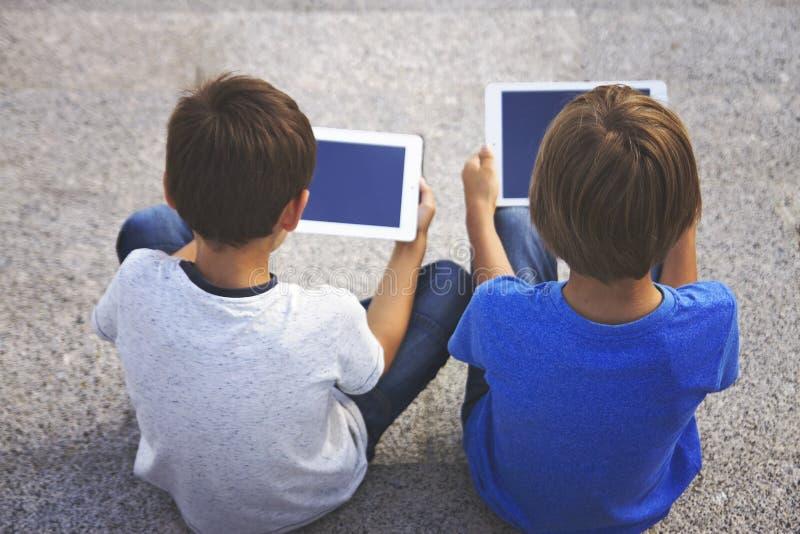 Crianças que sentam-se com computadores das tabuletas Vista traseira Educação, aprendendo, tecnologia, amigos, conceito da escola fotos de stock