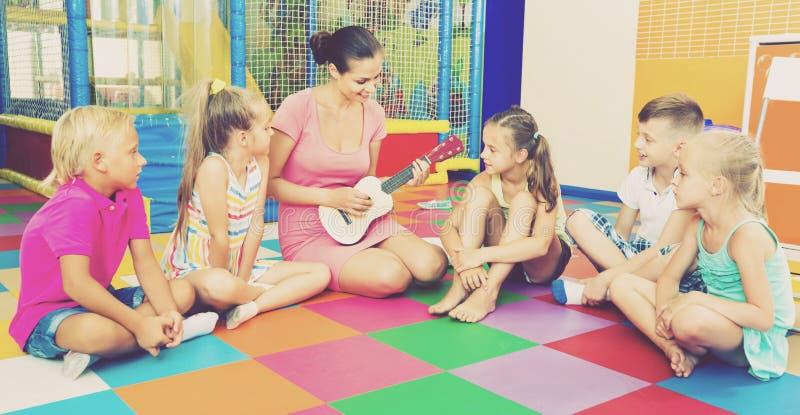 Crianças que sentam-se com professor e que escutam a música na classe foto de stock royalty free