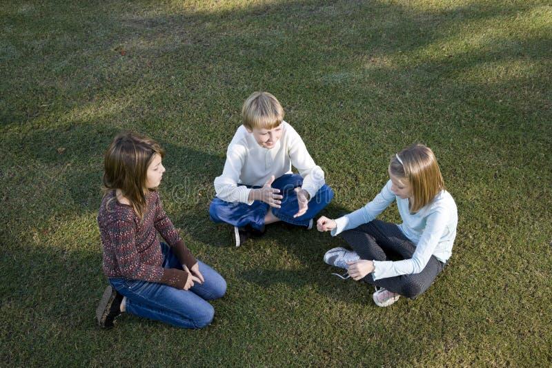 Crianças que sentam-se em um círculo na fala da grama imagens de stock