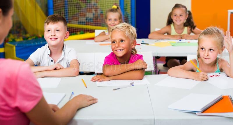 Crianças que sentam-se junto e que estudam na classe na escola fotos de stock