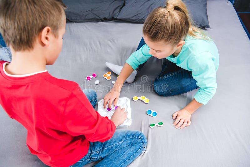 Crianças que sentam-se na cama e no jogo imagens de stock