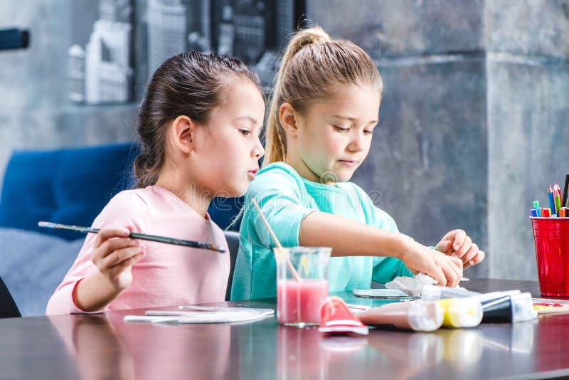 Crianças que sentam-se na tabela e em animais de pintura fotografia de stock royalty free