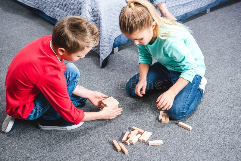Crianças que sentam-se no tapete e no jogo foto de stock
