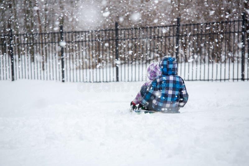 Crianças que Sledding na queda de neve do inverno foto de stock royalty free