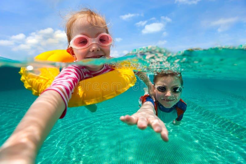 Crianças que têm a natação do divertimento em férias de verão imagem de stock