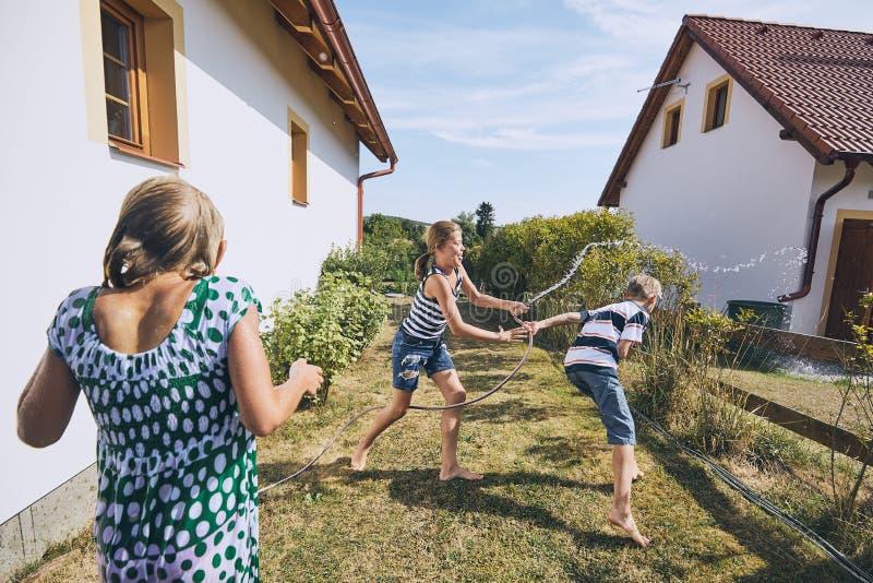 Crianças que têm o divertimento com espirro da água foto de stock royalty free