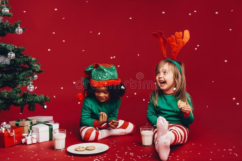 Crianças que têm o divertimento que come cookies do Natal imagem de stock