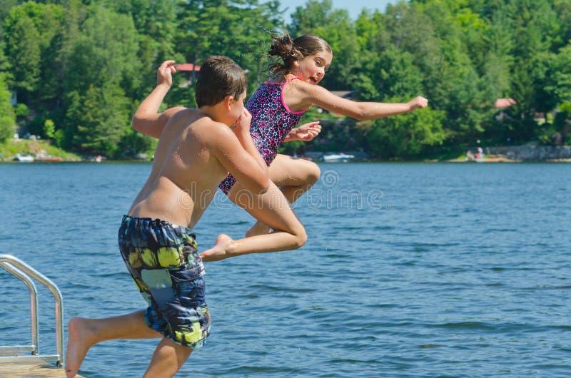 Crianças que têm o divertimento do verão que salta fora da doca no lago fotografia de stock