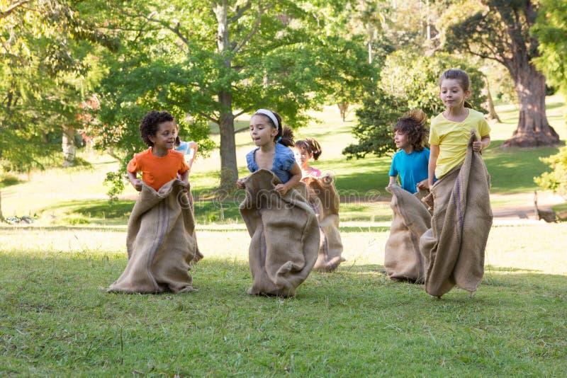 Crianças que têm uma raça de saco no parque imagem de stock royalty free