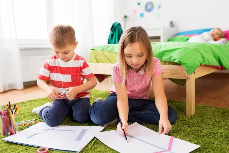 Crianças que tiram e que fazem ofícios em casa fotografia de stock