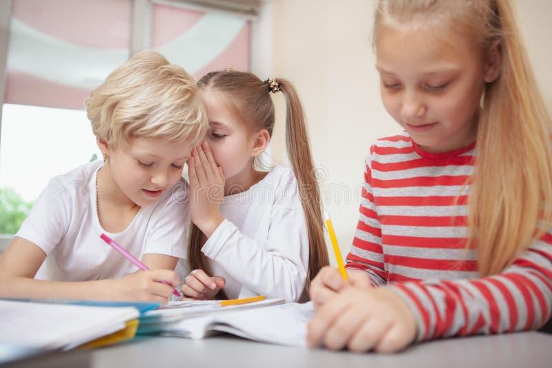 Crianças que tiram na classe de arte da escola primária foto de stock