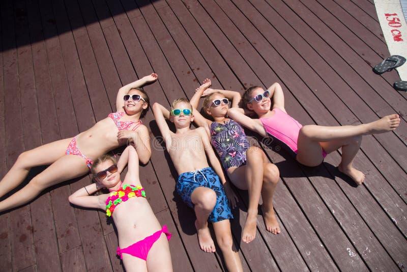 Crianças que tomam sol no recurso imagens de stock royalty free